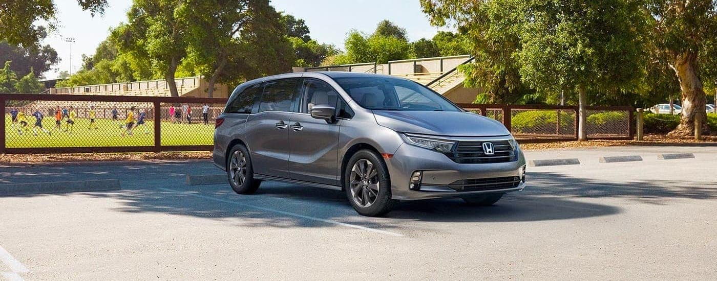 A gray 2021 Honda Odyssey is parked in front of a soccer field.