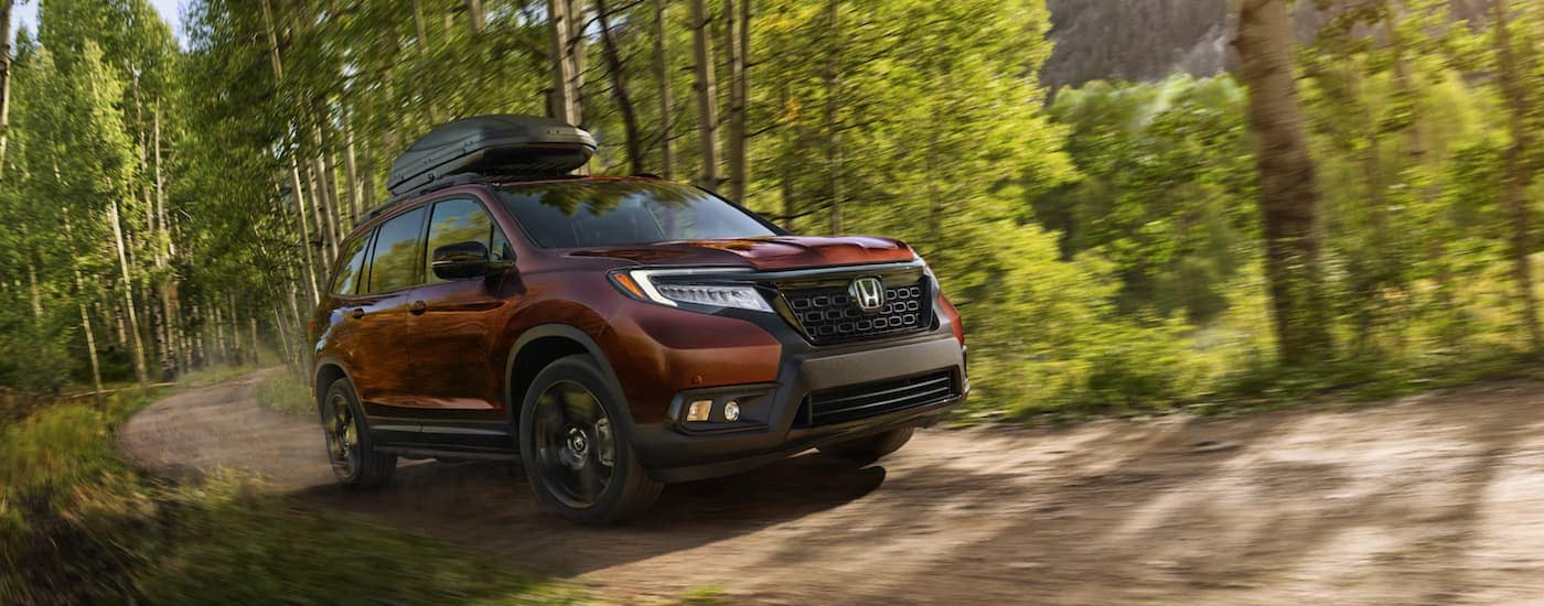 A burgundy 2021 Honda Passport with a roof cargo box is driving through the woods.