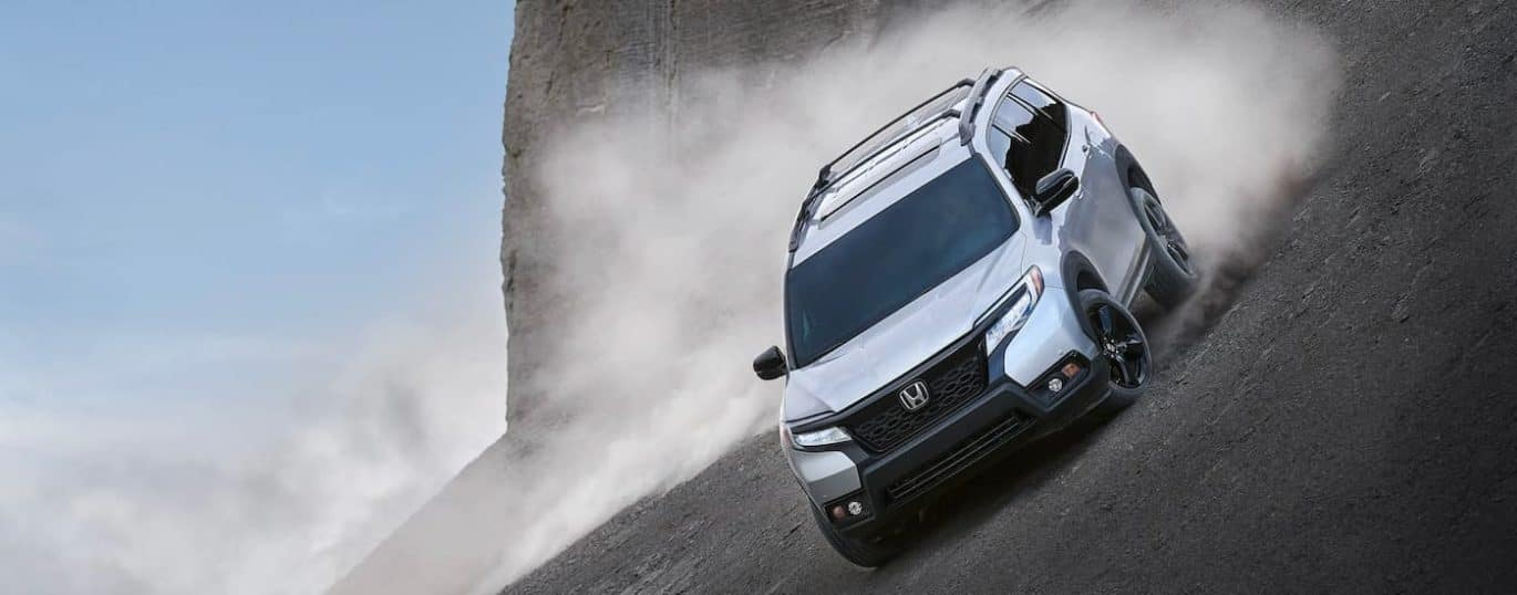 A silver 2021 Honda Passport Elite is shown driving on a steep hill kicking up dust.