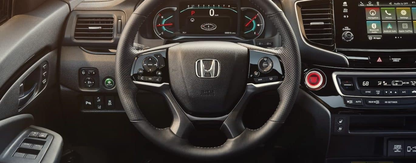 The steering wheel and controls are shown in a 2021 Honda Passport Elite.