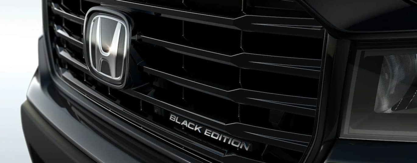 A close up shows the chrome badging and grille on a black 2021 Honda Ridgeline Black Edition.