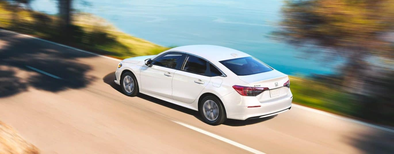 A white 2022 Honda Civic LX is shown driving past a lake and trees.