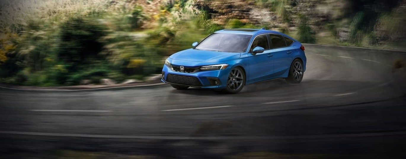 A blue 2022 Honda Civic Hatchback is shown driving on a winding road.