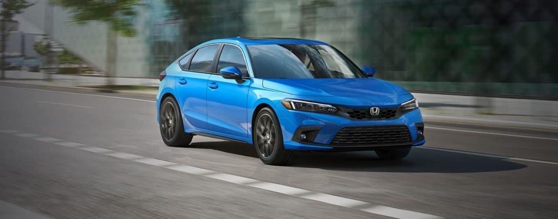 A blue 2022 Honda Civic Hatchback is shown driving down a city street.