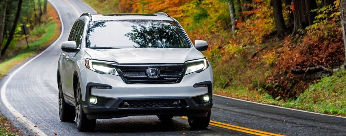 A white 2021 Honda Pilot Black Edition is driving down a winding road.