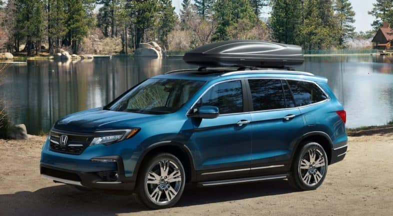 A blue 2021 Honda Pilot Elite is parked in front of a lake after leaving a Rochester Honda Pilot dealer.