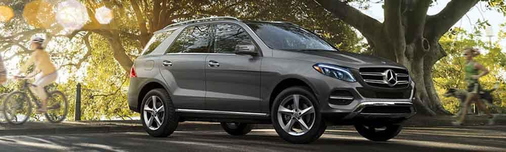 2018 Mercedes-Benz GLE parked at a park with people running and biking by