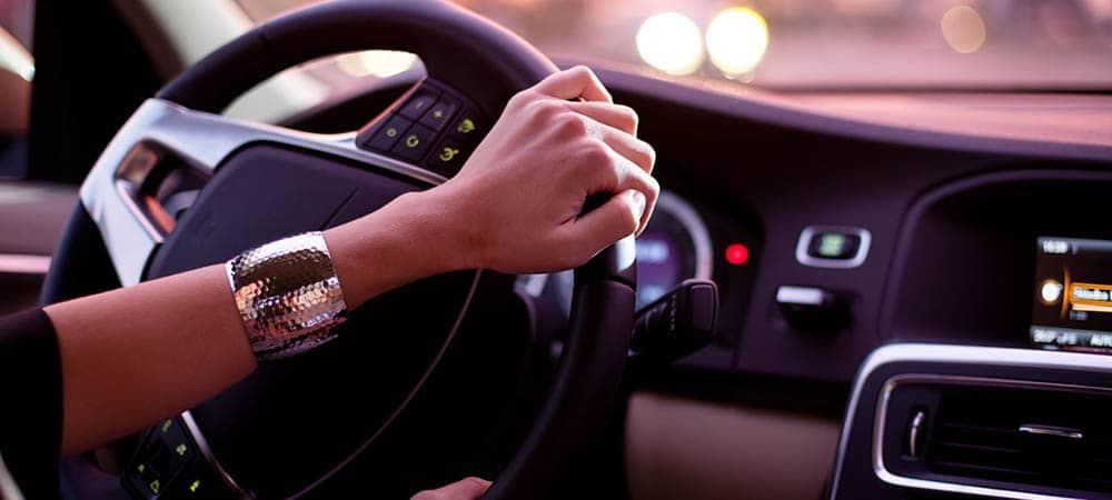 Woman driving with hands on the steering wheel while on the phone