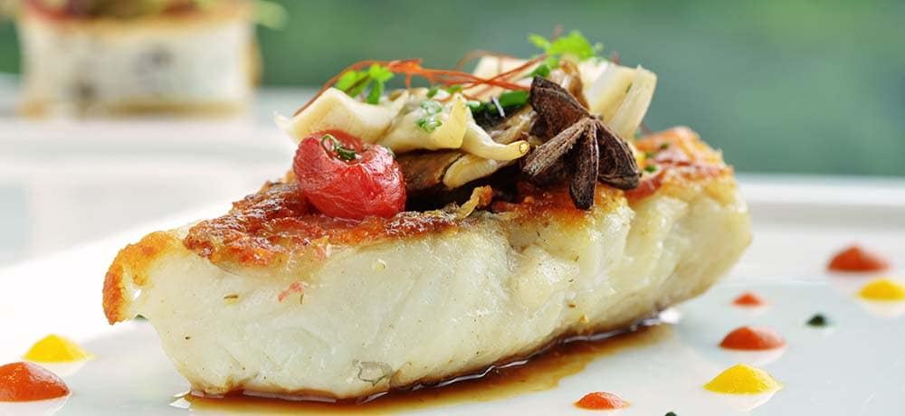 grilled fish on dinner plate with decorative sauces