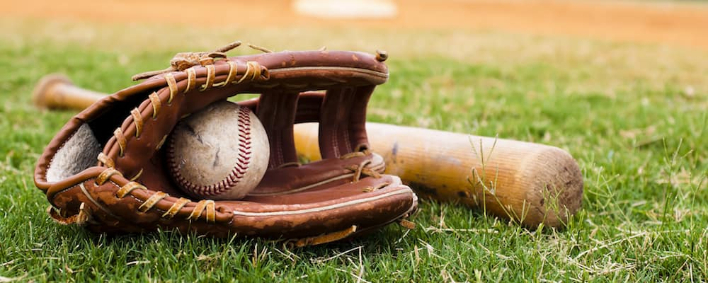 baseball glove and bat on field