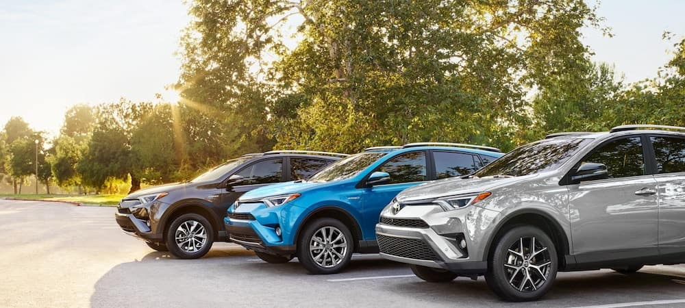 RAV4s left to right - Gray XLE Hybrid, Blue Limited Hybrid, and Silver SE