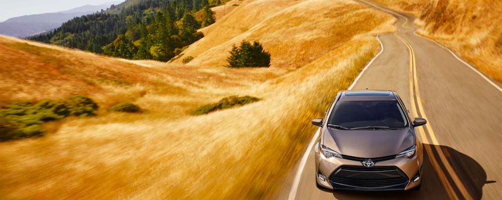 2019 Toyota Corolla in silver, driving down the open road.