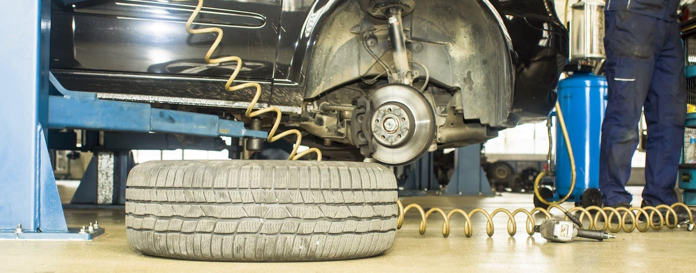 A mechanic is changing a tire on a black car at a tire shop near you.