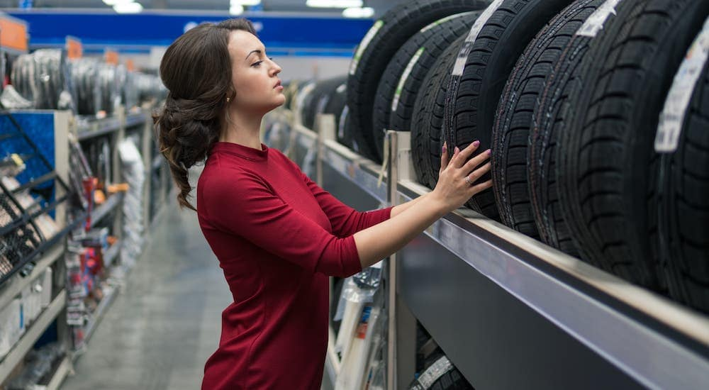 A woman is looking at tires on a rack at a Romeoville tire shop.