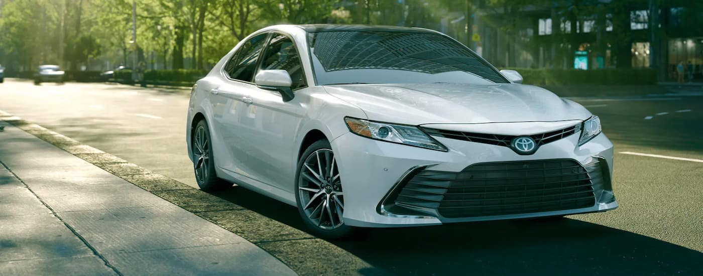 A white 2021 Toyota Camry is parked on a city street with trees after leaving a Toyota dealer near me.