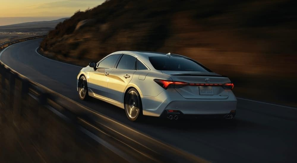 A silver 2021 Toyota Avalon is driving on a narrow road around a corner after leaving a Toyota dealer near me in Lexington, KY.