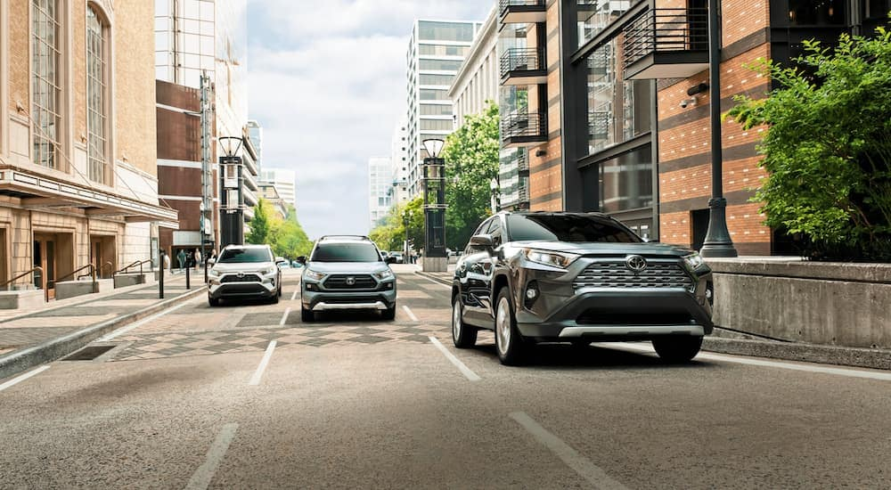 Three 2021 Toyota RAV4s are driving on a multi-lane city street.