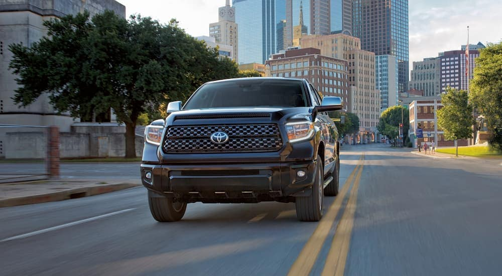 A black 2021 Toyota Tundra is driving away from city buildings.