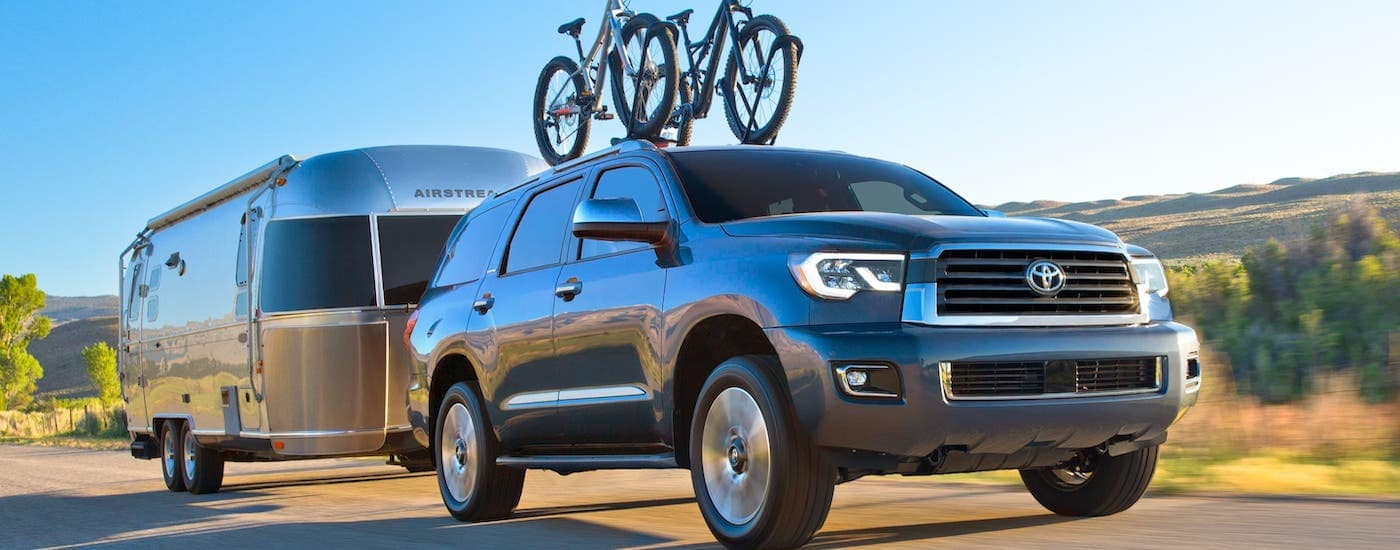 A gray 2020 Toyota Sequoia with bikes on the roof is towing an Airstream camper on a highway near Romeoville, IL.