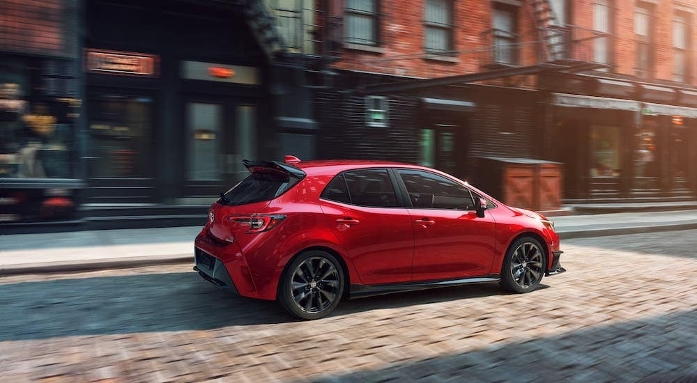A red 2021 Toyota Corolla Hatchback from a Toyota dealer near you is driving on a cobblestone road.