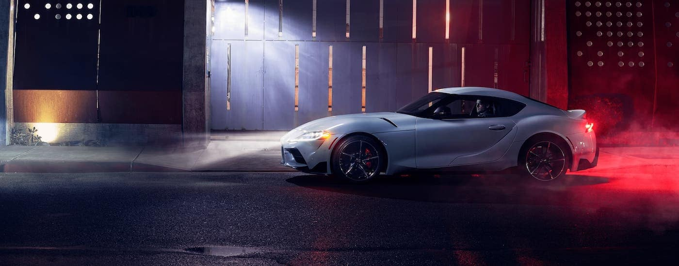 A white 2021 Toyota Supra is shown from the side at night.