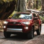 A red 2021 Toyota 4Runner is driving on a dirt road in the woods.
