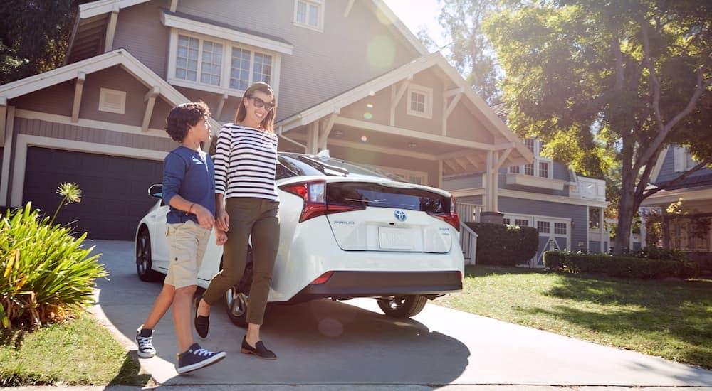 A mom and son are walking past a white 2021 Toyota Prius parked outside a home after returning from a Toyota dealer.