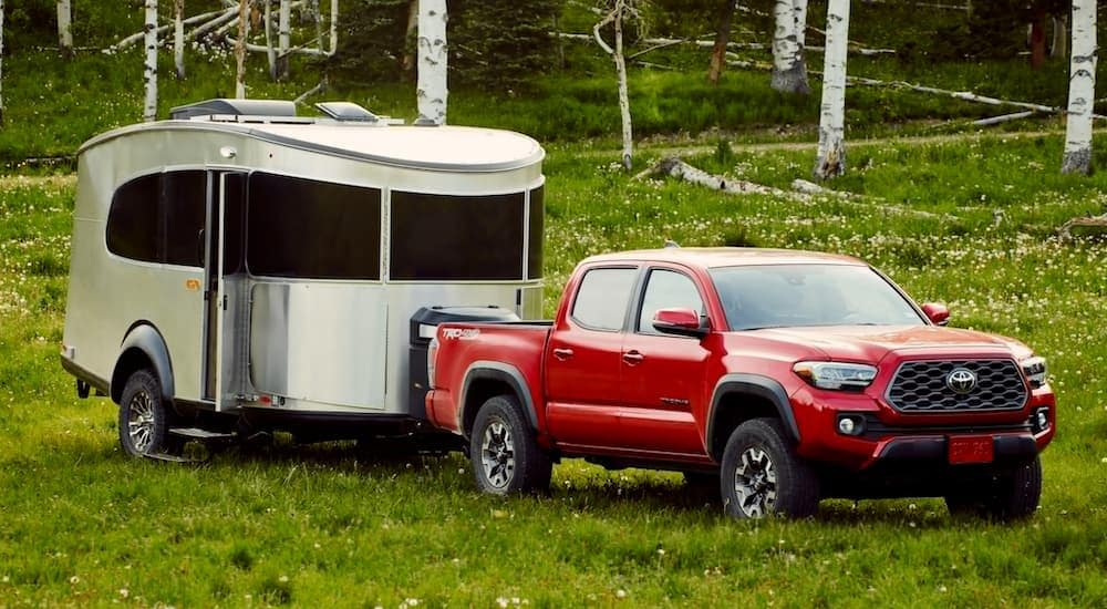 A red 2021 Toyota Tacoma is towing a camper on grass near Romeoville, IL.