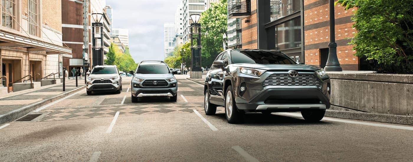 Three Toyota SUVs, all 2021 Toyota RAV4s, are driving on a city road across three lanes.