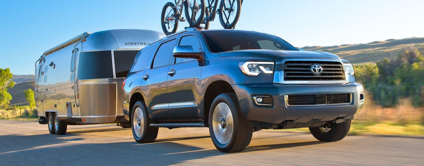 A grey 2021 Toyota Sequoia is towing an Airstream and has bikes on the roof rails.