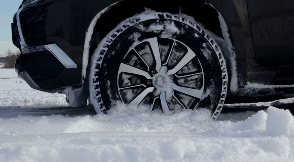 A closeup shows a car tire in the snow.