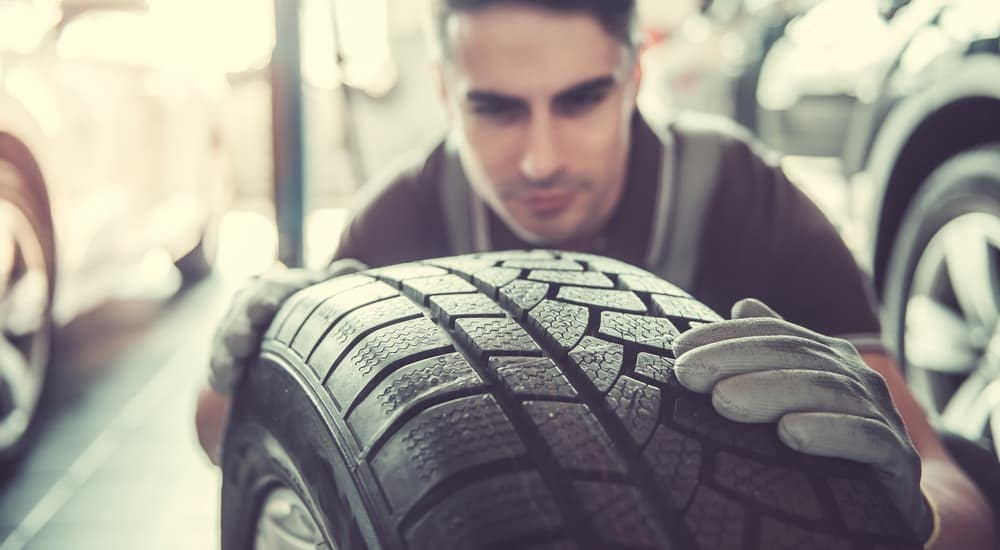 A technician is looking closely at a tire at a tire shop near me.