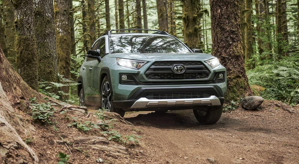 A light green 2021 Toyota RAV4 is off-roading on a trail in the woods.