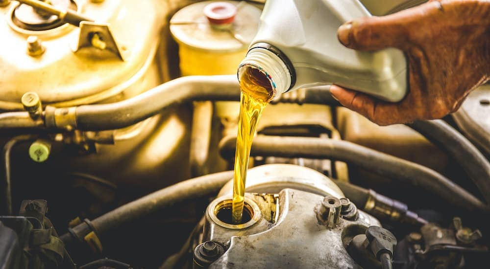 A mechanic is filling an engine with oil after an oil change near you.