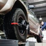 A mechanic is aligning the tires on a vehicle.
