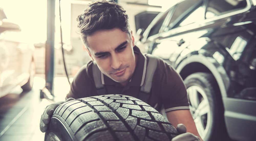 A mechanic is inspecting the tread of a tire at a tire shop near you.