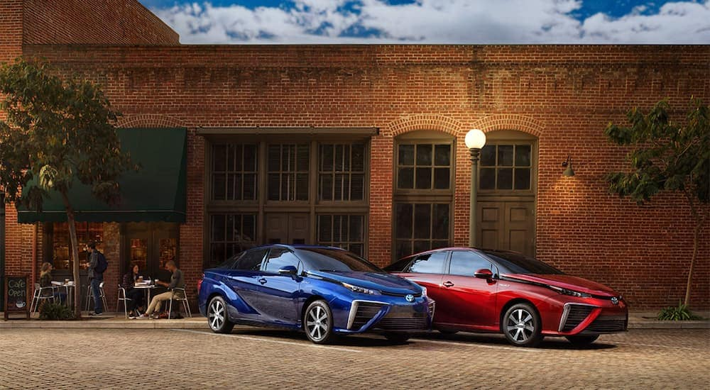 A blue and a red 2021 Toyota Mirai are parked in front of a brick building angled right.