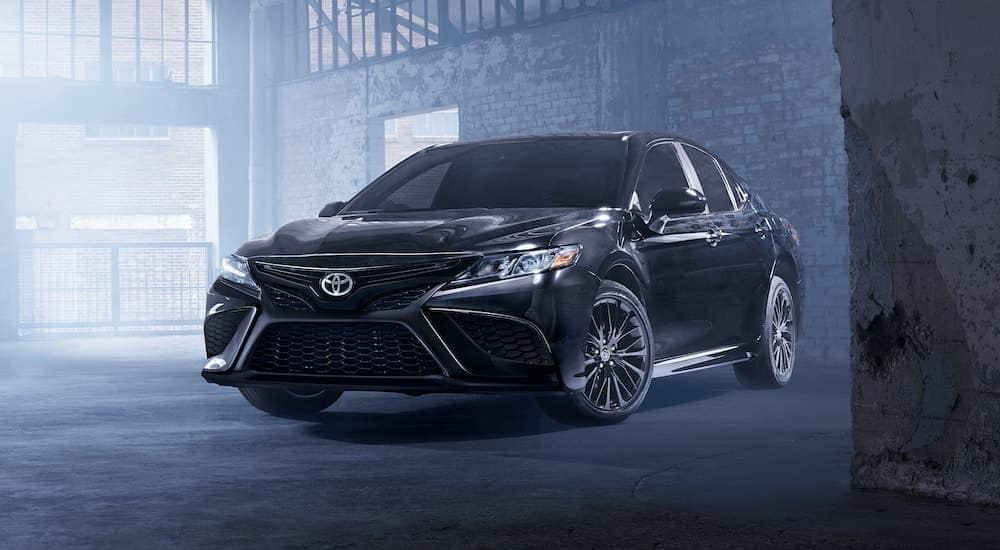 A black 2021 Toyota Camry Hybrid SE Nightshade Edition is parked in an empty warehouse.