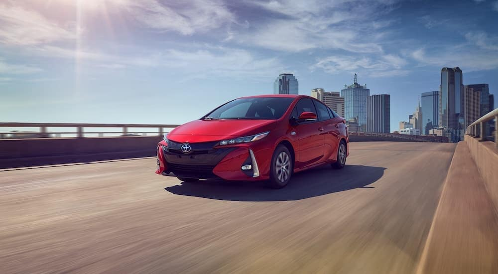 A red 2021 Toyota Prius Prime Limited is driving down the highway away from the city.