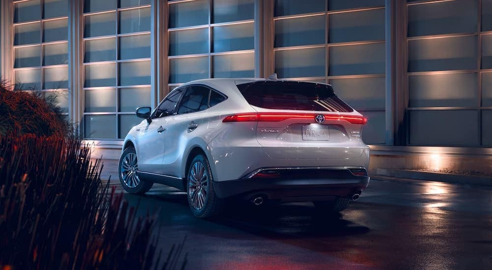 A popular Toyota hybrid, a white 2021 Toyota Venza Limited, is shown from the rear outside a glass building.