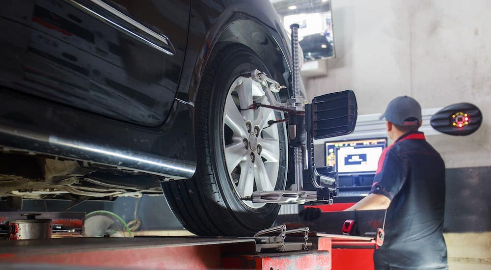 A mechanic is performing a Wheel Alignment on a black car that is on a lift.
