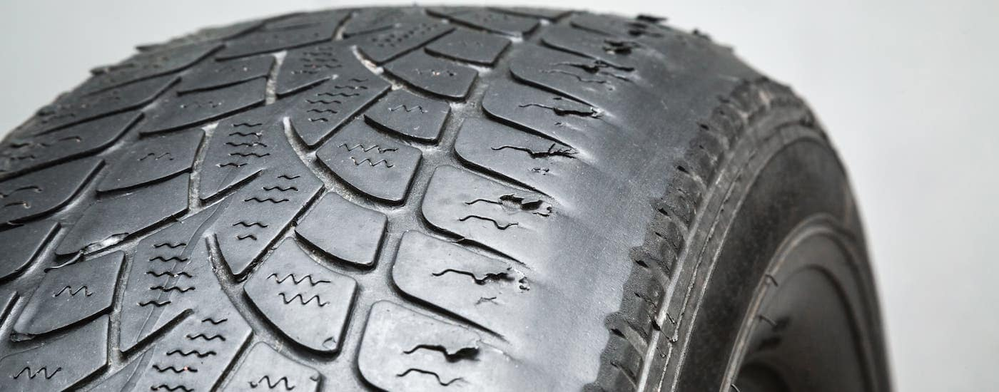 A tire with irregular wear is shown against a light gray background.