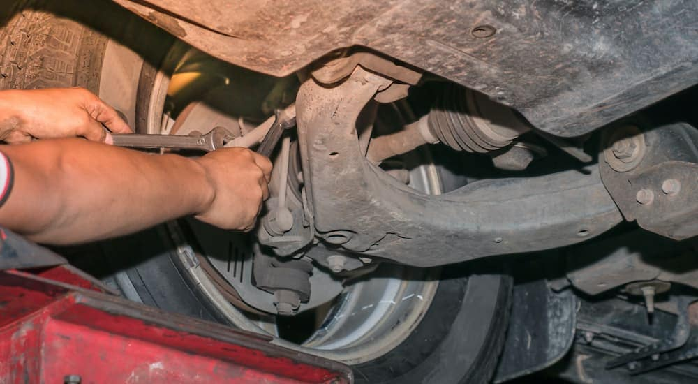 A close up is shown of a mechanic adjusting the suspension during a wheel alignment.