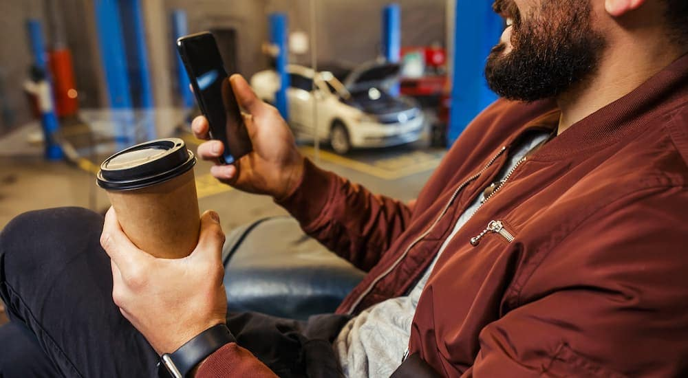 A close up is shown of a man with a coffee and cell phone in a waiting room.