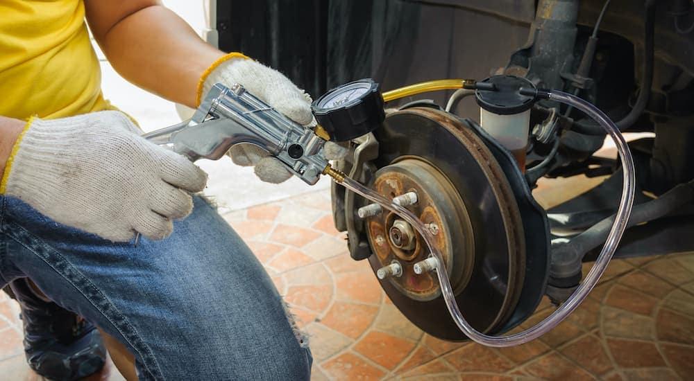 A close up shows a mechanic bleeding the brake fluid during a brake service.