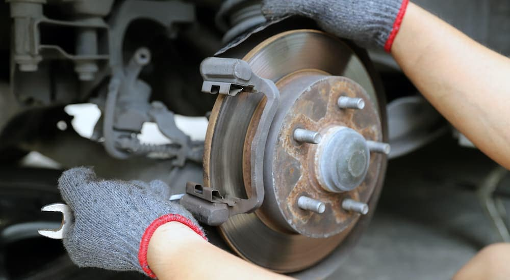 A close up shows gloved hands removing a caliper during a brake service.