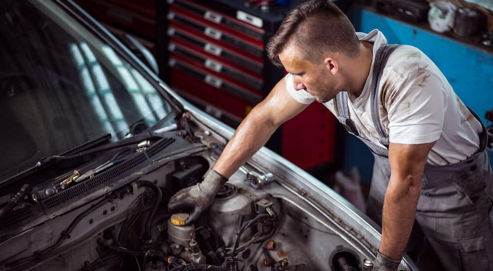 A mechanic is shown removing the brake fluid reservoir cap on a vehicle