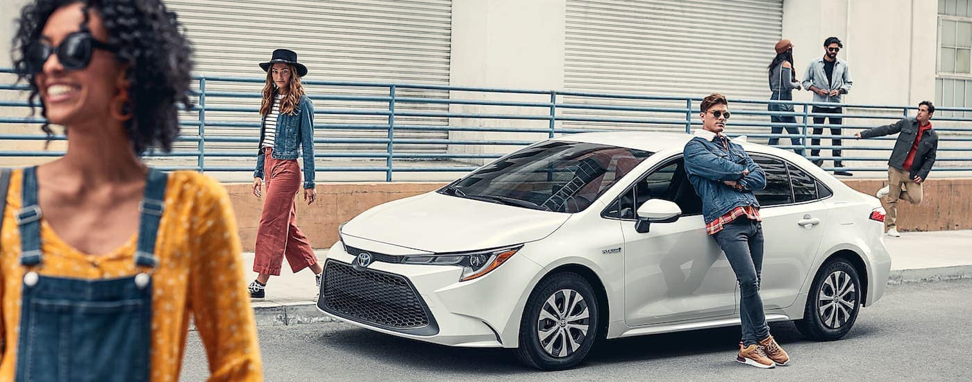 A group of friends are hanging out around a white 2020 Toyota Corolla.