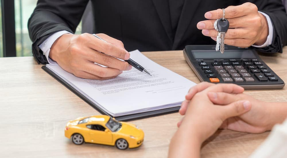 A close up shows a sales person holding up a set of car keys while pointing at loan documents with a ballpoint pen.