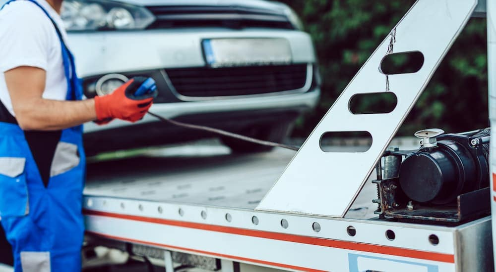 A close up is shown of a car being pulled on to a trailer.